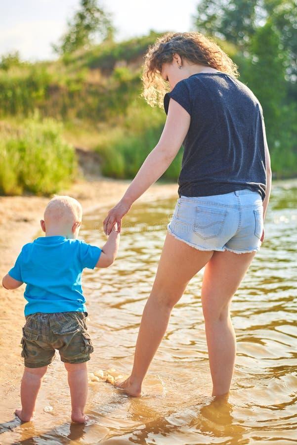 Mama i jej syn chodzimy wzdłuż brzeg rzekiego na gorącym letnim dniu zdjęcia stock