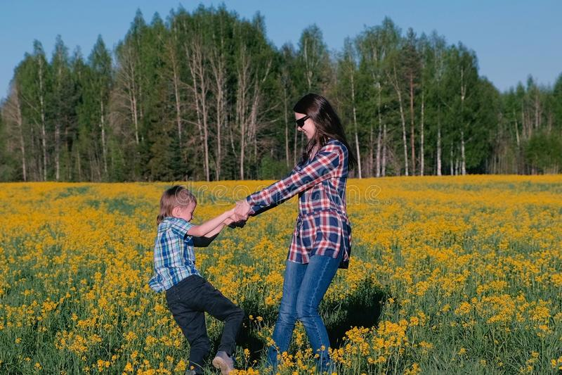 Mama i syn wirujemy mienie ręki na polu z żółtymi kwiatami Rodzinny spacer w wiośnie zdjęcia stock