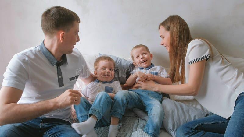 Mama i tata bawić się z bliźniaczymi chłopiec berbeciami kłama na łóżku Rodzinny dzień wolny zdjęcia stock
