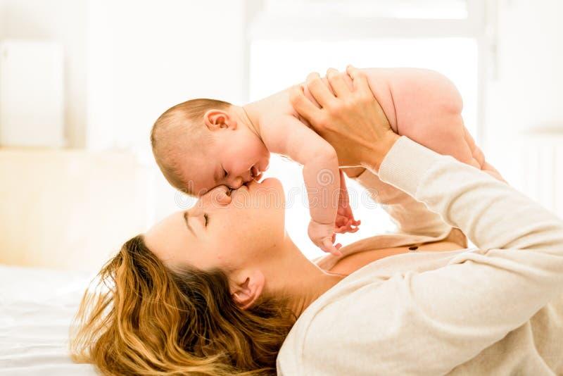 Mama küsste ihre neugeborene Tochter liebevoll, Konzept der Mutterschaft und glückliches Familienleben stockbild