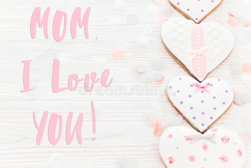 Mama kocham ciebie tekst na różowych ciastek sercach na biały nieociosany drewnianym fotografia stock