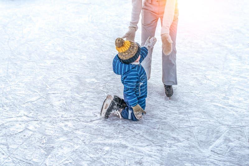 Mama mit Baby-Junge 3-5 Jahre alt, lerne Zug, fahre Winterstadtrand, Eislaufen Das Kind steht auf, fällt auf Schlittschuhe lizenzfreies stockfoto