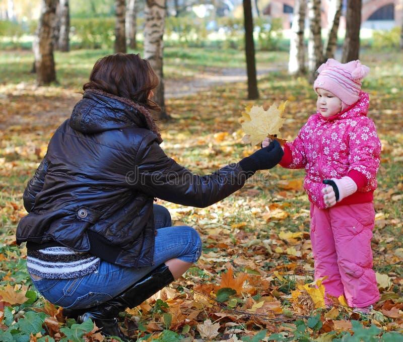 Mama mit einem Tochterweg im Herbstpark stockbild