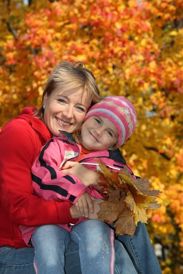 Mama mit einer Tochter im Herbstpark lizenzfreies stockbild