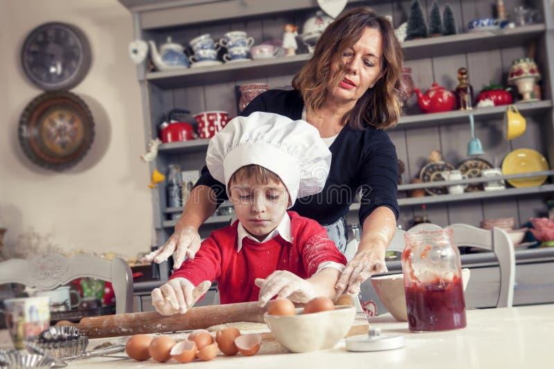 Mama pomaga jej syna przygotowywa słodkiego jedzenie obrazy stock