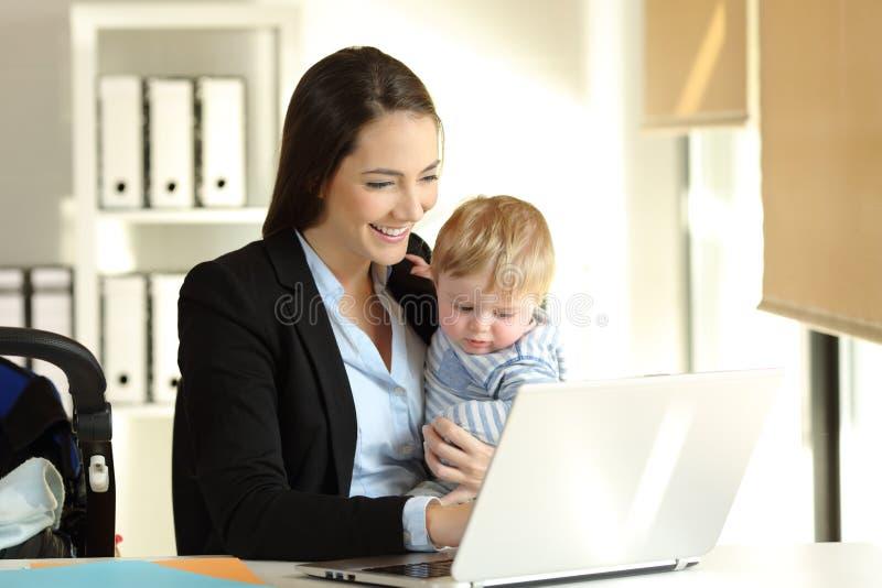 Mama pracuje z jej dziecko synem przy biurem fotografia stock