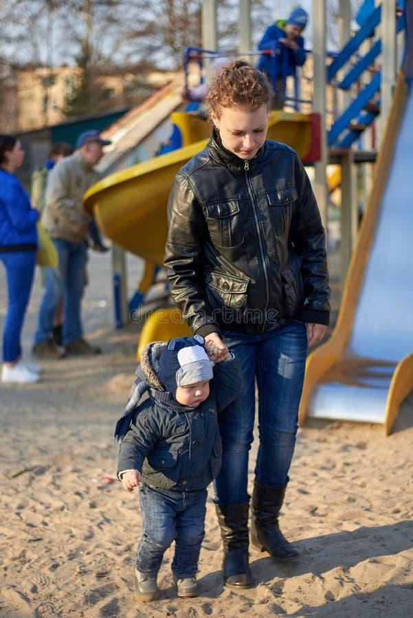 Mama prowadzi jej małego syna z boiska przez złego zachowania obraz stock
