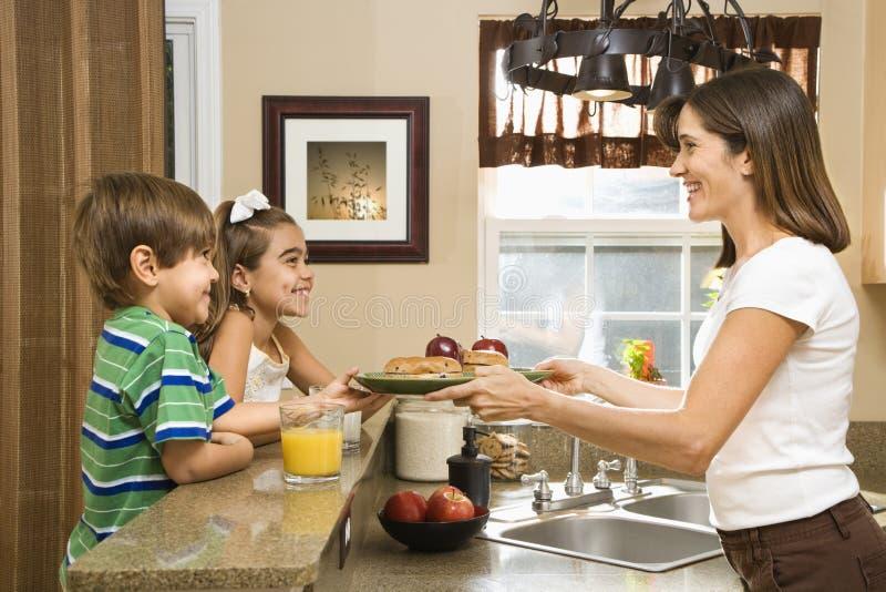 Mama que da a cabritos el desayuno. foto de archivo libre de regalías