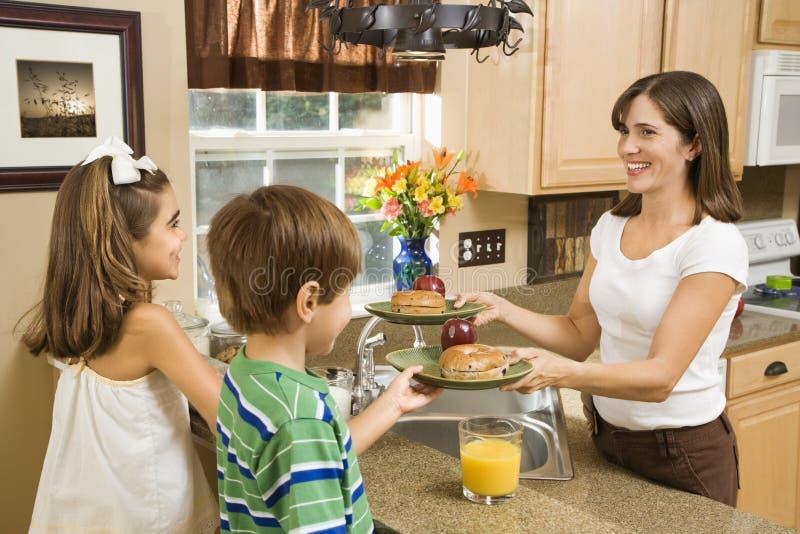 Mama que da a cabritos el desayuno. imagen de archivo