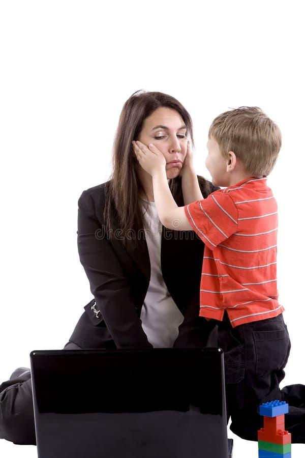 Mama que intenta trabajar jugar del hijo foto de archivo libre de regalías