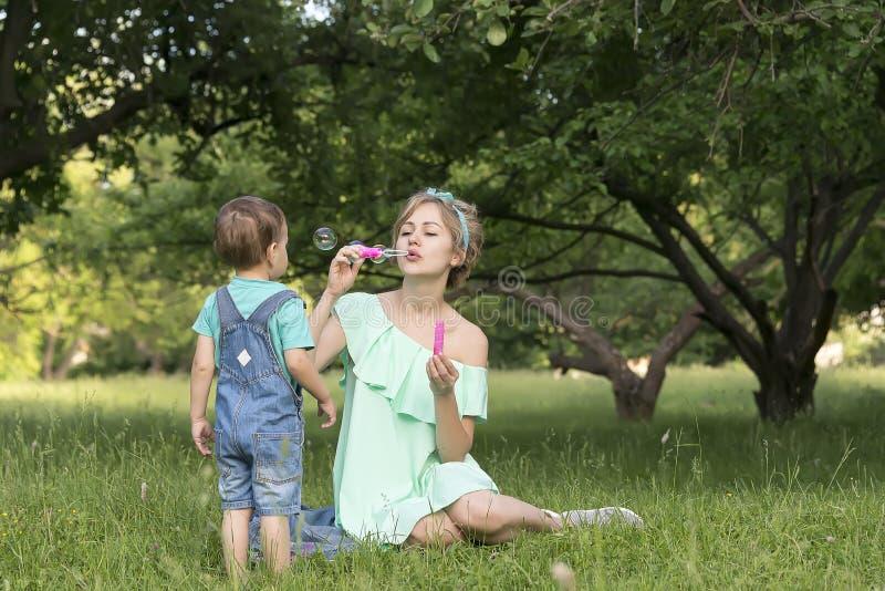 Mama, syn i mydlani bąble w parku fotografia royalty free