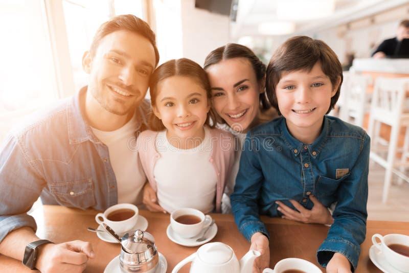 Mama, tata, córka i syn pozuje wpólnie na kamerze w kawiarni, obrazy royalty free
