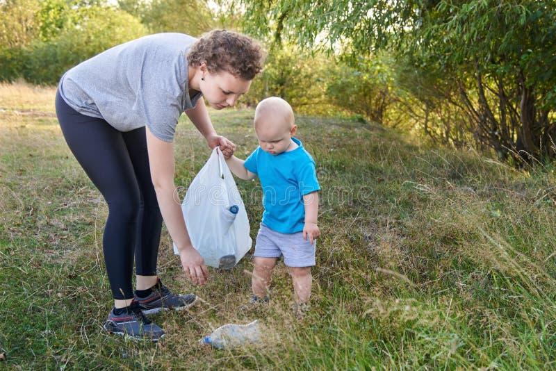 Mama uczy jej syna czyścić w górę grata w naturze Temat zanieczyszczenie środowiska śmieci obraz royalty free