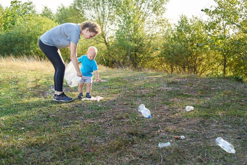 Mama uczy jej syna czyścić w górę grata w naturze Temat zanieczyszczenie środowiska śmieci obrazy stock