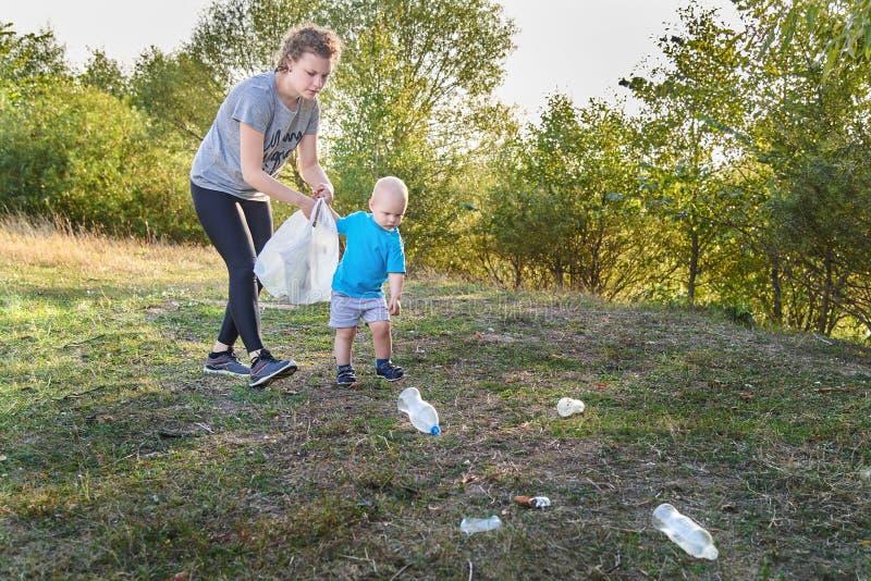 Mama uczy jej syna czyścić w górę grata w naturze Temat zanieczyszczenie środowiska śmieci zdjęcie royalty free
