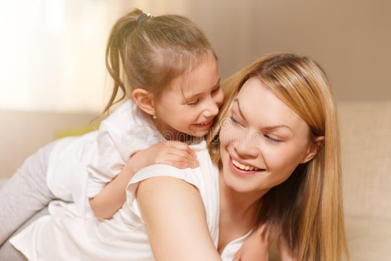 Mama und ihr nettes Tochterkindermädchen spielen, lächeln und umarmen Glückliches Mother& x27; s-Tag stockbild