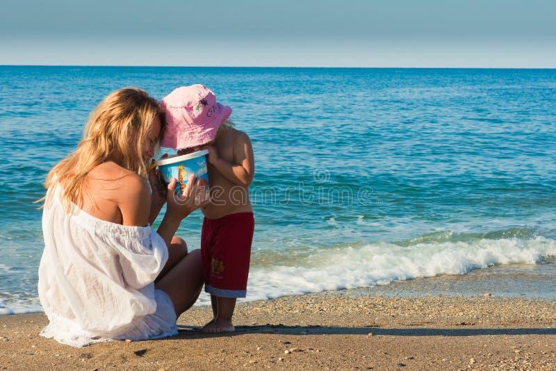 Mama- und Sohnspiel auf dem Strand stockfotografie