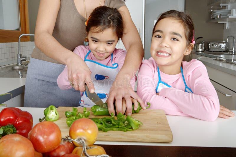 Mama und Töchter, die Veggies hacken lizenzfreies stockfoto