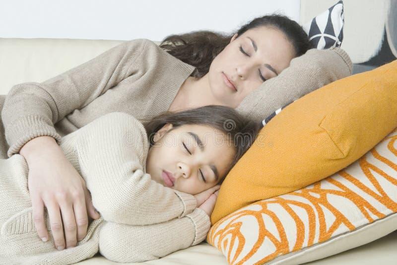 Mama und Tochter, die auf Couch schlafen lizenzfreies stockfoto