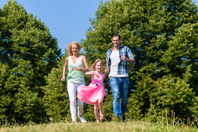 Mama, Vati und Tochter, die auf einem Feldweg laufen stockbilder
