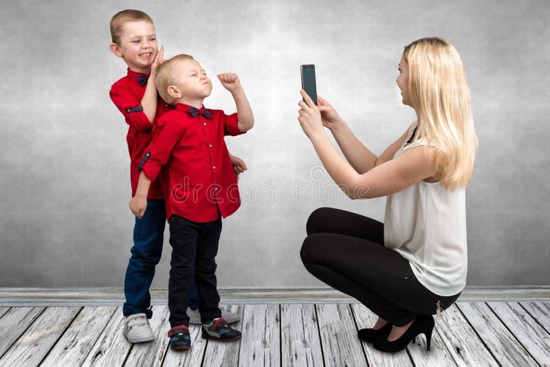 Mama wp8lywy na telefonu komórkowego dwa synach Dziecko sztuki zabawa i rozgrymasza zabawa czas wolny obrazy royalty free
