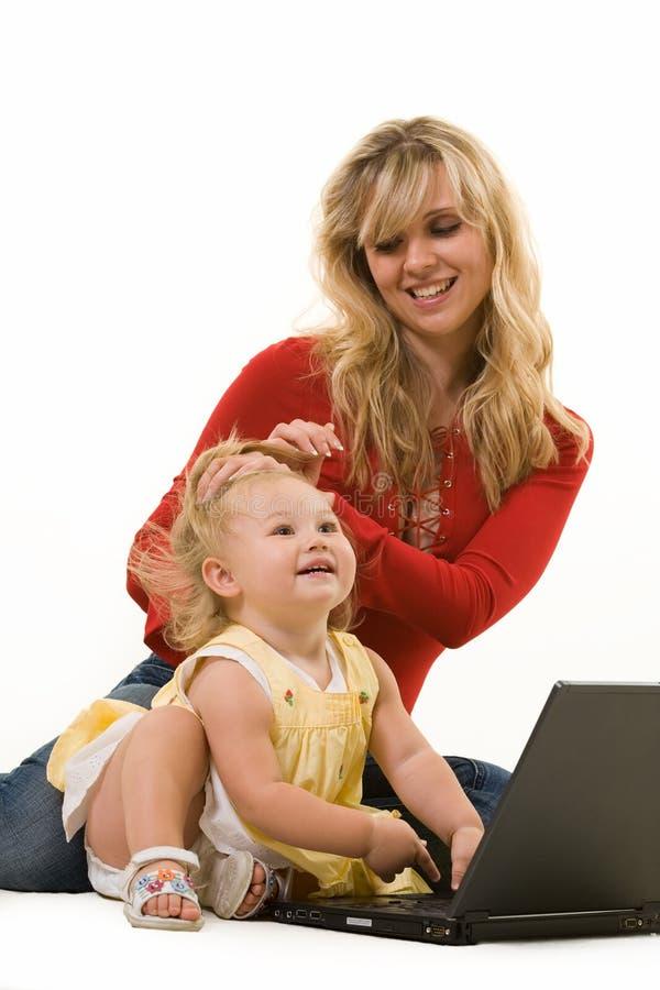 Mama y bebé con la computadora portátil fotos de archivo