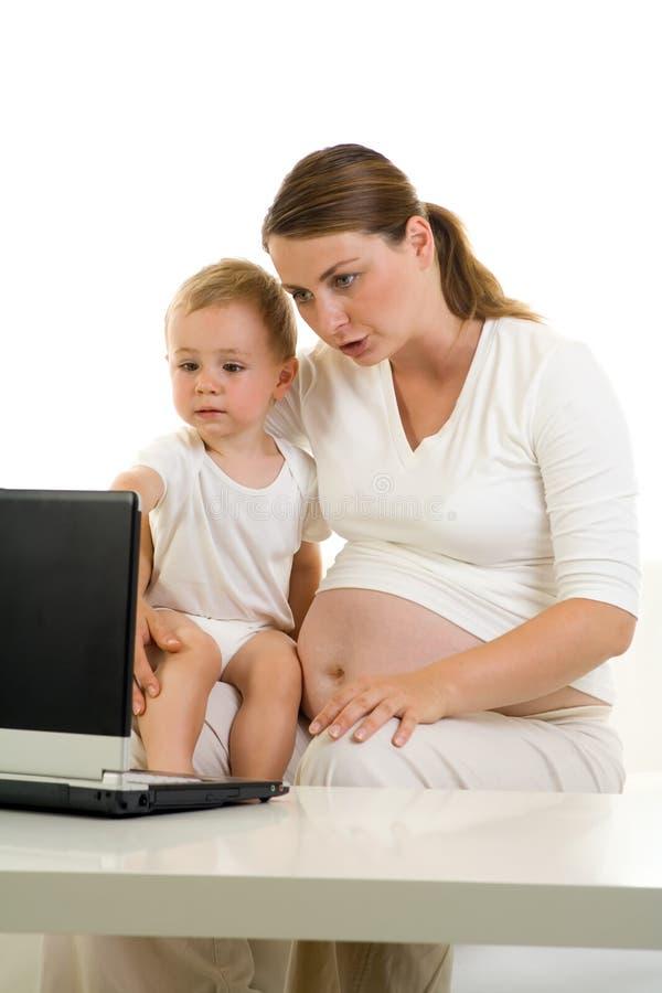Mama y niño embarazados con la computadora portátil imagen de archivo libre de regalías