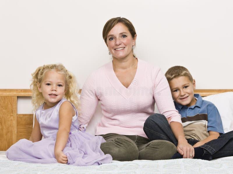 Mama y niños que se sientan en cama fotografía de archivo libre de regalías