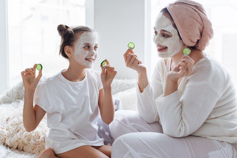 Mama z jej córką robi glinianej twarzy masce obraz stock