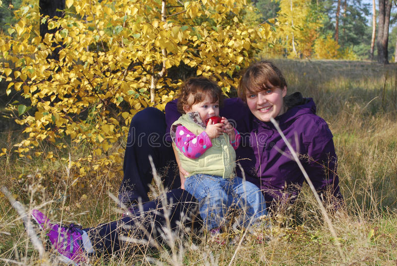 Mama z jej córki sittingt na trawie obraz stock