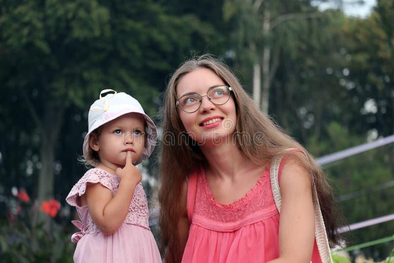 Mama z tajemniczym spojrzeniem i zdziwiona mała dziewczynka stawiamy palec jej wargi obraz royalty free