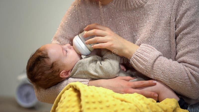 Maman alimentant le petit bébé mignon de la bouteille, tenant tendrement le fils, l'amour et le soin photographie stock libre de droits