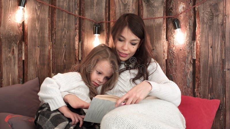 Maman assez jeune lisant un conte de Noël à sa fille mignonne s'asseyant sur le sofa enveloppé dans des couvertures photos libres de droits