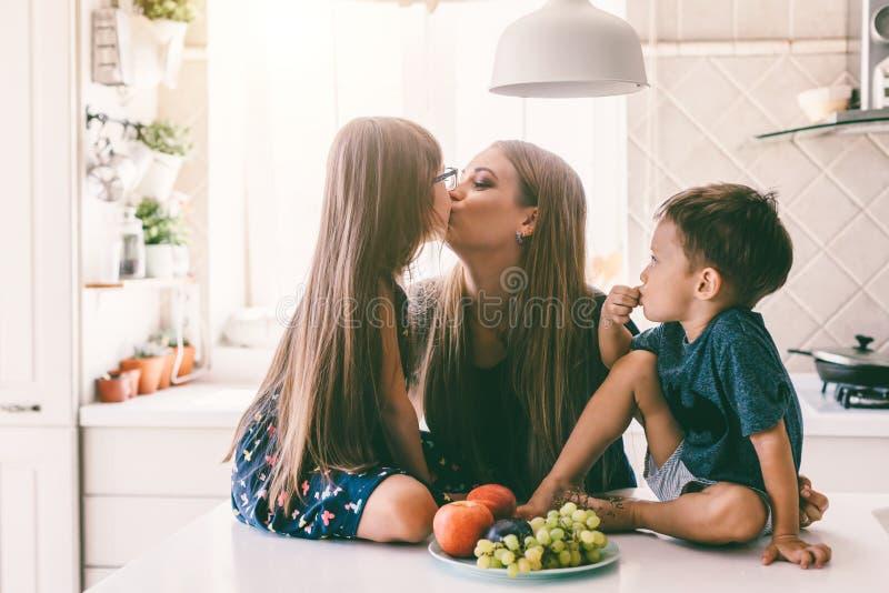 Maman avec des enfants mangeant sur la table de cuisine photos stock