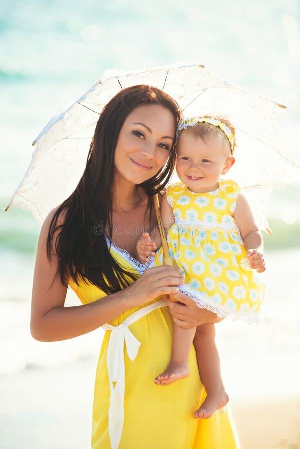 Maman avec la fille sous un parapluie blanc de dentelle un jour chaud photos stock