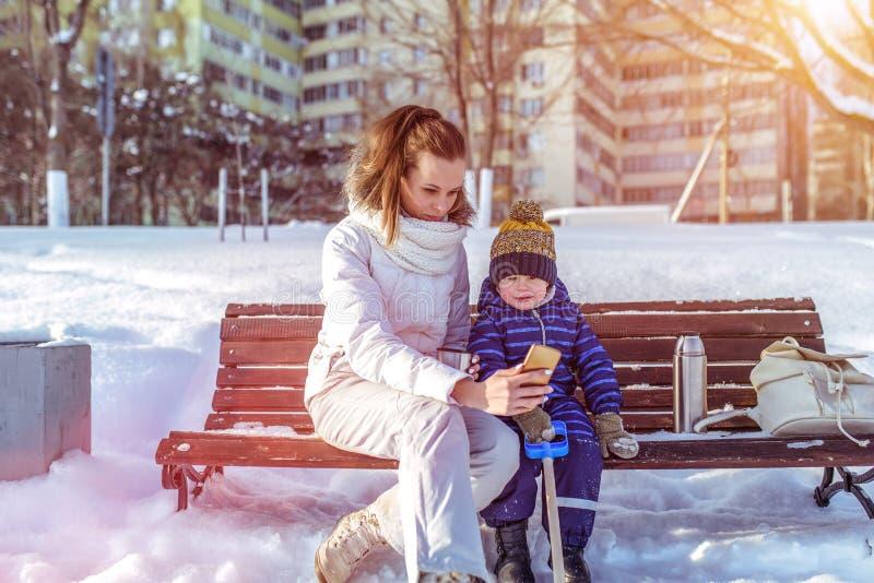 Maman avec un fils de garçon 3 années, pendant l'hiver dans une paire sur un banc, air frais Parc de ville de week-end de vacance photographie stock