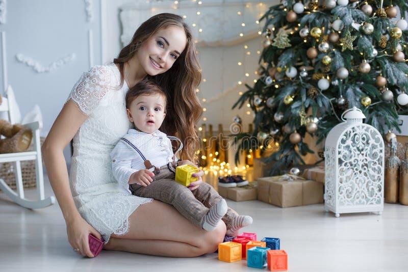 Maman avec un petit fils près d'un bel arbre dans sa maison jouant avec les cubes colorés photo stock