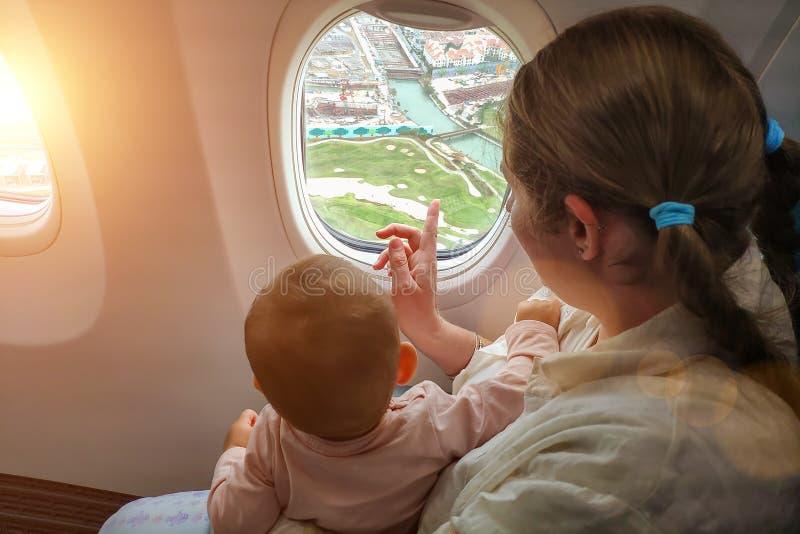 Maman avec un petit regard d'enfant la fenêtre de l'avion à la terre Voyage avec la fille infantile au-dessous d'un an images libres de droits
