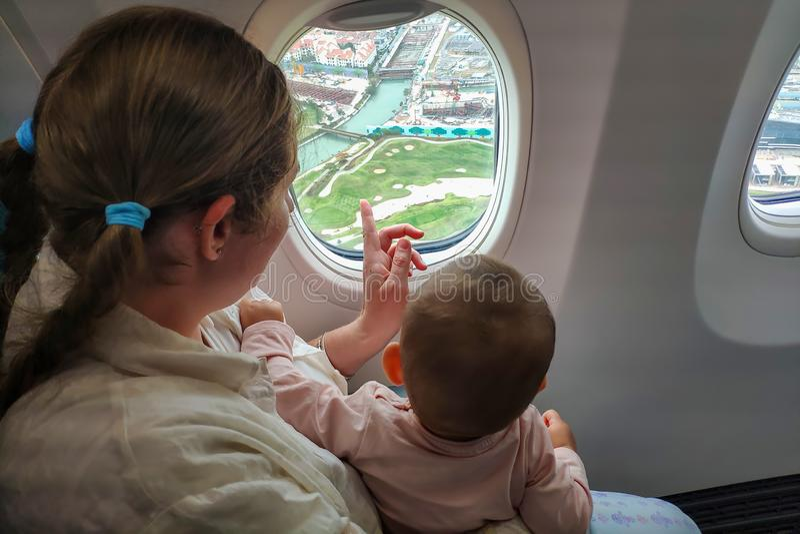 Maman avec un petit regard d'enfant la fenêtre de l'avion à la terre Voyage avec la fille infantile au-dessous d'un an images stock