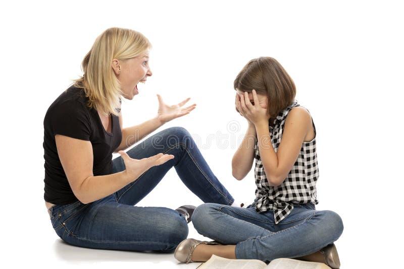 Maman criant à la fille de l'adolescence, d'isolement sur le fond blanc image stock