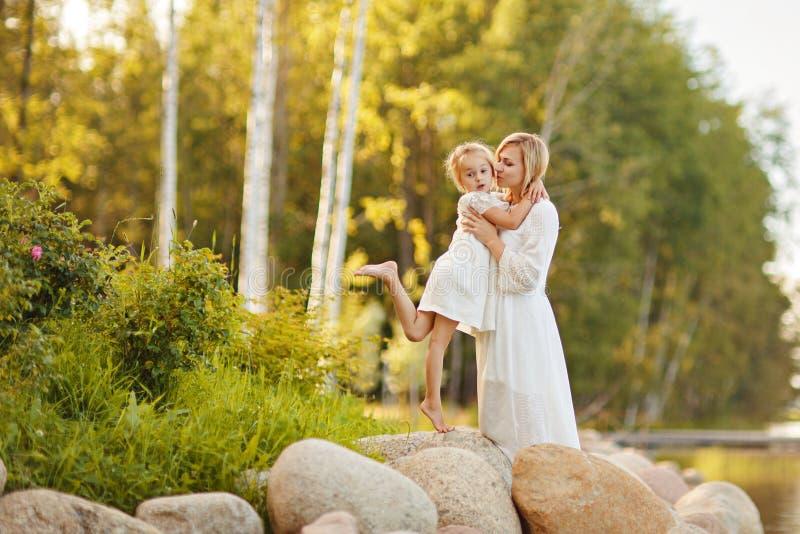 Maman dans une robe blanche avec sa fille s'asseyant sur de grandes roches dessus photos libres de droits