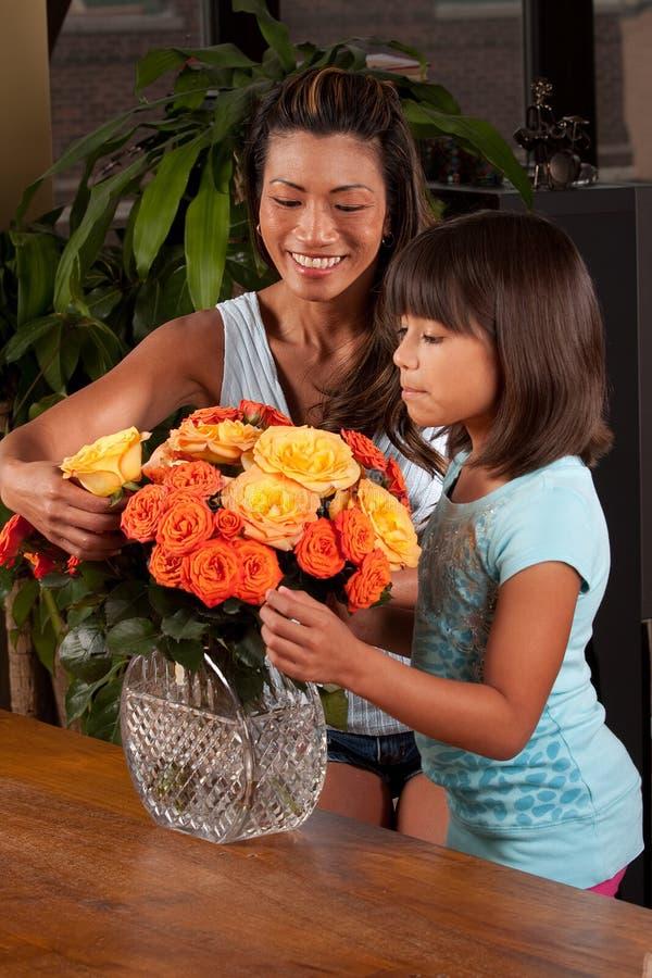 Maman de aide de fille avec des fleurs images libres de droits