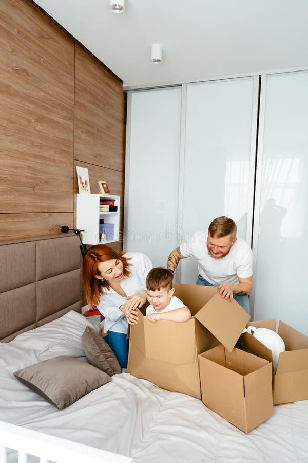 Maman de papa et petit jeu de fils dans la chambre à coucher avec les boîtes de papier photographie stock libre de droits