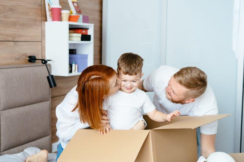 Maman de papa et petit jeu de fils dans la chambre à coucher avec les boîtes de papier photo stock