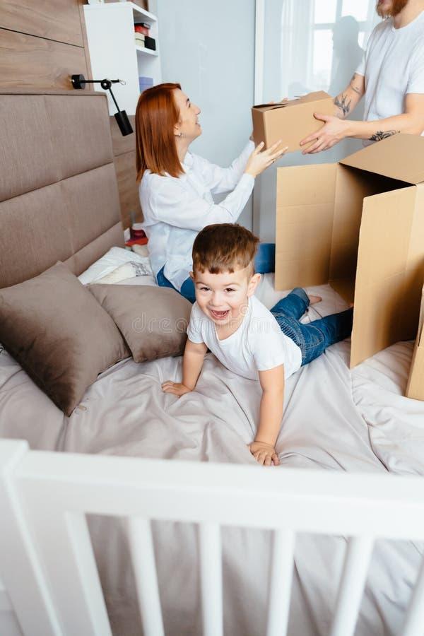 Maman de papa et petit jeu de fils dans la chambre ? coucher avec les bo?tes de papier photo stock