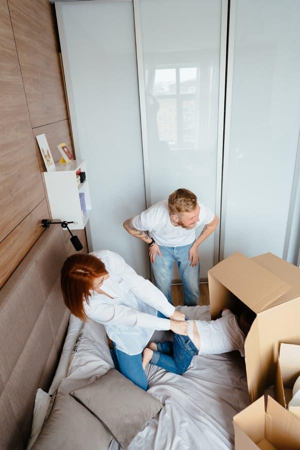 Maman de papa et petit jeu de fils dans la chambre ? coucher avec les bo?tes de papier photographie stock libre de droits