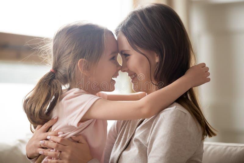 Maman de sourire de embrassement de fille mignonne d'enfant touchant des nez ayant l'amusement images stock