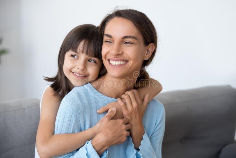 Maman de sourire et fille mignonne d'enfant embrassant le regard dans l'avenir image libre de droits