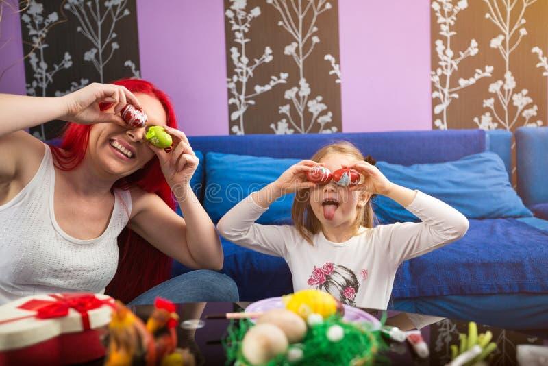 Maman de sourire et oeufs de pâques espiègles gais de fille ensemble photographie stock libre de droits
