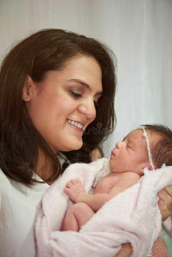 Maman de sourire tenant le bébé nouveau-né photographie stock libre de droits